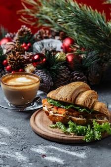Новогодний завтрак с круассанами. новогодний круассан с красной рыбой и авокадо. новый год и