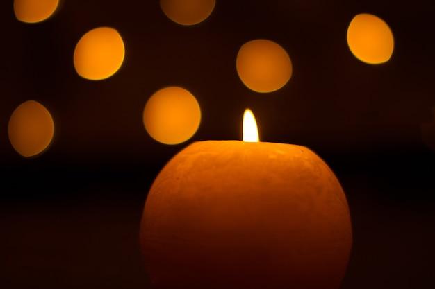 Новогодние горящие свечи с красивым размытым боке из гирлянды, тёплым тусклым светом, мягким фокусом.