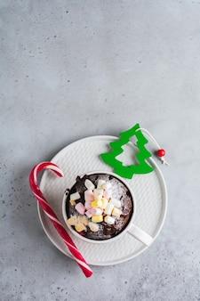 ヴィンテージの灰色の表面の質感にマグカップで電子レンジで調理された新年のチョコレートケーキ