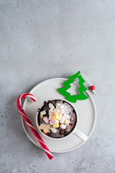 New year's chocolate cake cooked in microwave oven in mug on vintage gray surface texture