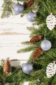 녹색 가문비나무 가지, 천연 원뿔, 크리스마스 장식으로 장식된 새해 크리스마스 배경. 흰색 나무 소박한 테이블입니다.