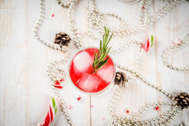 New year's, christmas drinks. red alcohol cocktail with cranberry, liqueur, rosemary, with ice. on a white table, with christmas candies, ornaments and pine cones. copyspace top view