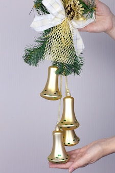 新年、クリスマスのおもちゃの鐘、鐘の円錐形の鐘、モミの枝と赤いボールのペア。白い背景の上の鐘。