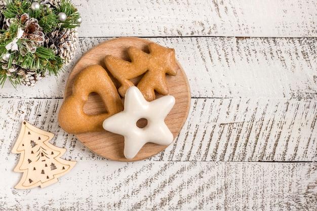 新年の作曲。白い木製の背景にジンジャーブレッドとクリスマスの装飾。クリスマス、冬、新年のコンセプト。フラットレイ、コピースペース付きの上面図。