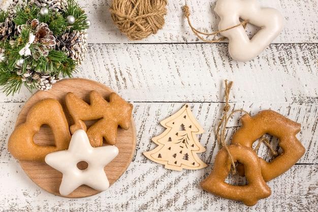 新年の作曲。ジンジャーブレッド、白い木製の背景に紙とクリスマスの装飾に包まれたギフト。クリスマス、冬、新年のコンセプト。フラットレイ、コピースペース付きの上面図。