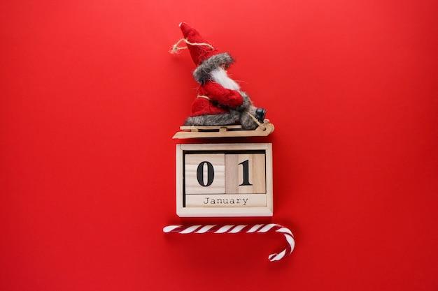 Новогодняя композиция. старый деревянный календарь с санта-клаусом на санях на красном. плоская планировка.