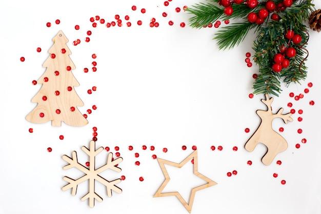 白いテーブルの上の新年の構成。クリスマスの飾り、松の枝、木製の雪の結晶、鹿、鐘、トウヒ、星と赤い輝き。上からの眺め。スペースをコピーします。