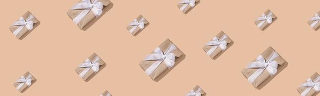 新年の作曲。砂色の背景にハードシャドウと白いリボンと紙のギフトボックスのトレンディな新年のパターン。フラットレイ、上面図。クリエイティブなミニマルなクリスマスアート。