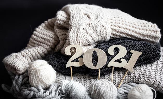 Новогодняя композиция с вязаными предметами и деревянным новогодним номером на темном фоне крупным планом.