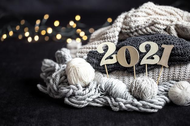 Новогодняя композиция с вязанными предметами и деревянным новогодним номером на темном фоне.