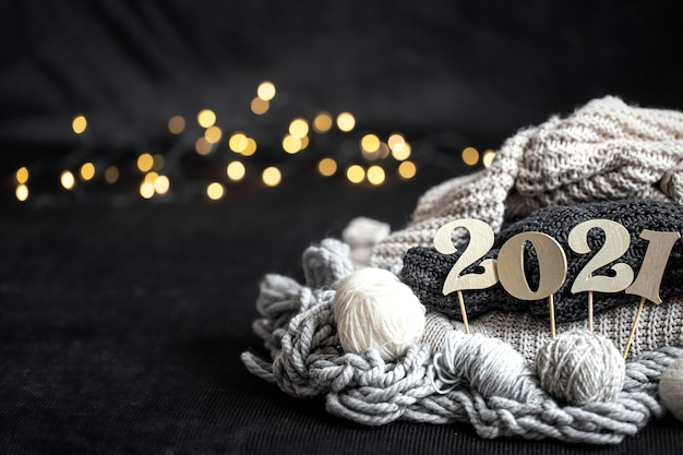 New year's composition with knitted items and wooden new years number on a blurred background.