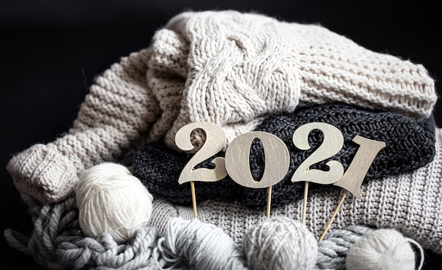 New year's composition with knitted items and wooden new years number on a dark background close up.