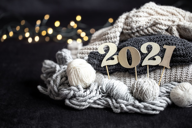 New year's composition with knitted items and wooden new years number on a dark background.