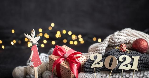 Новогодняя композиция с деревянным новогодним номером и рождественскими украшениями на темном фоне.