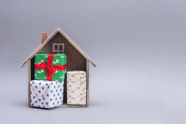 Новогодняя композиция. деревянный дом с подарками на сером фоне.