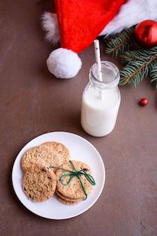 牛乳、白い皿、チョコレートが入ったサンタの新年のクッキー。サンタの帽子、クリスマスツリーのおもちゃ、クリスマスツリーの小枝。フラットレイ