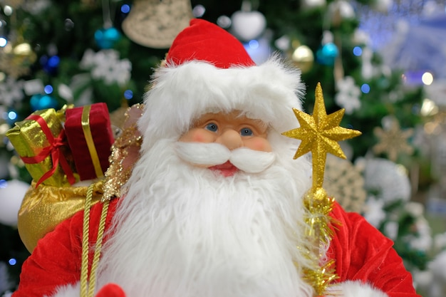 New year's decor santa claus close-up on the background of the christmas tree. christmas toy santa claus.