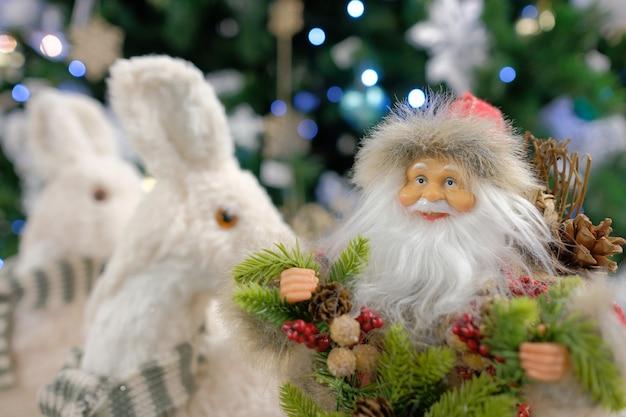 Новогодний декор санта-клауса крупным планом на фоне елки. новогодняя игрушка дед мороз.