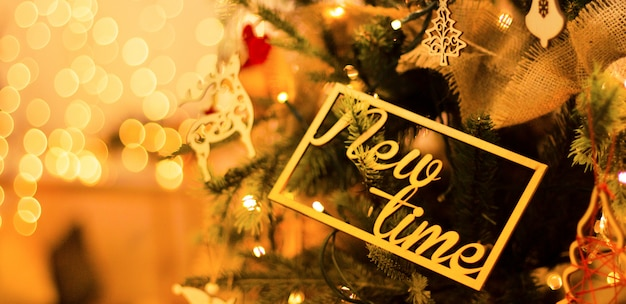 New year's decoration on the christmas tree with beautiful luminous yellow blurs