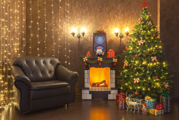 New year's decoration of the interior of the living room with a fireplace and a leather armchair.