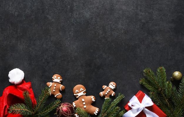 Новогоднее украшение шапкой деда мороза, мандаринами и пряниками