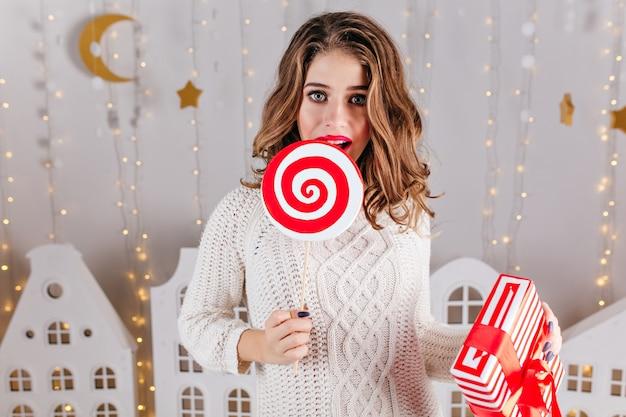 골판지 집과 크리스마스 화환의 형태로 새해 장식, 거대한 막대 사탕을 먹는 갈색 머리 여자. 흰색 따뜻한 스웨터에 매력적인 모델의 초상화