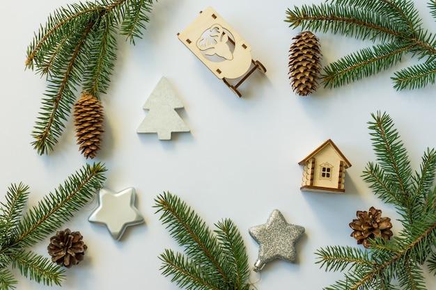 コーンと緑の枝、銀の星、木製のそり、おもちゃの家で新年のお祝いの背景。フラットレイアウト。上面図。