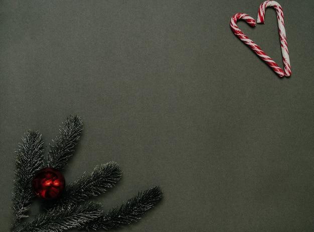 新年のフラットリー。無地の緑の背景にクリスマスツリーの枝、コーン、ボール、キャラメルの杖のフレーム。広告またはテキスト用の空のスペース。