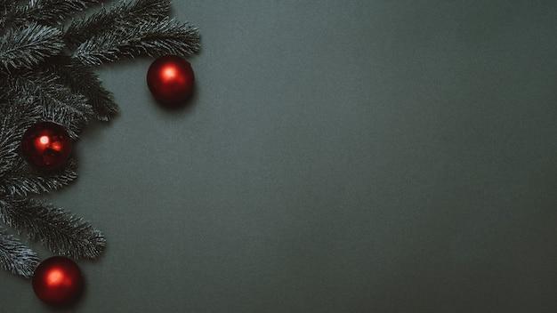 新年のフラットリー。無地の緑の背景にクリスマスツリー、コーン、ボール。広告またはテキスト用の空のスペース。