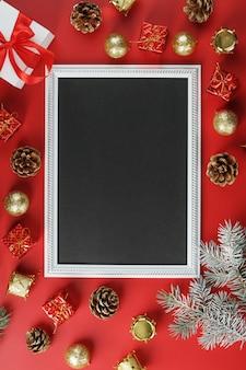 Новогодняя рамка с новогодними игрушками, еловыми ветками и подарками в окружении на красном фоне