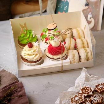 Новогодние подарочные наборы конфет. коробка кексов и макарон в подарок на рождество. кексы со сливочно-сырным кремом и арахисово-карамельной начинкой и торты макаруны с мандариновой начинкой.