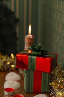 빨간색 포장의 새해 선물은 양초가있는 선반에 놓여 있습니다.