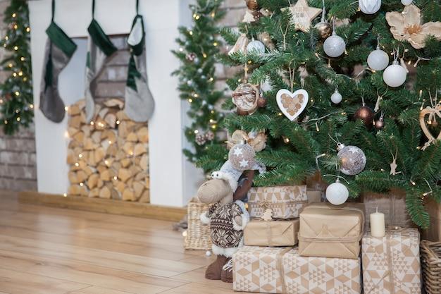 お祝いのクリスマスツリーの下で新年の贈り物