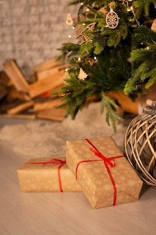 New year's gifts and wicker basket under beautiful christmas-tree with fireplace hearth and grey brick wall background.
