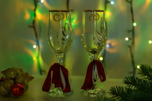 New year's glasses on the background of a luminous garland in green.