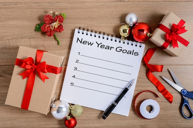 New year's goals list written on notebook with gift box