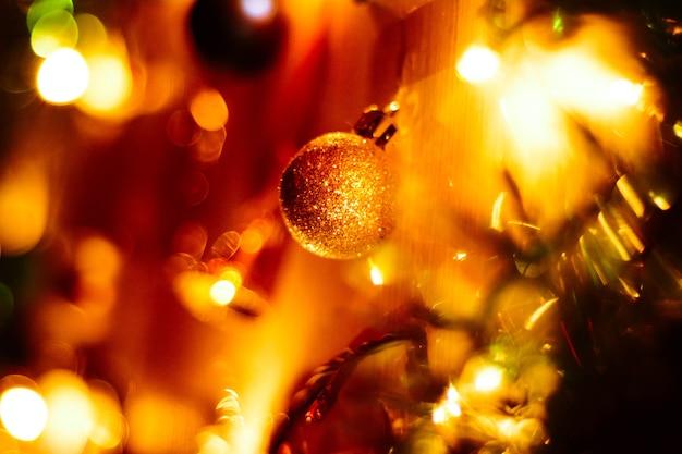 Новогодний золотой шар для елки в огнях гирлянды