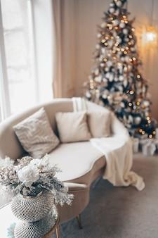 Новогодний праздничный букет украшений в серебряной вазе на прикроватном стеклянном столике на белом диване и украшенная елка с гирляндами