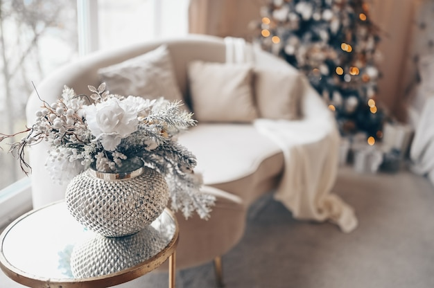 New year's holiday decoration bouquet in silver vase on bedside glass table against white sofa and decorated christmas tree with garland lights