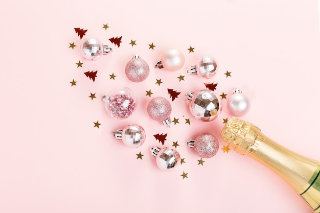 New year's holiday with bottle of champagne on pink background. christmas, new year. festive flat lay, top view, copy space