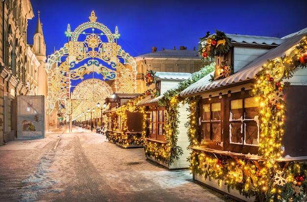 Новогодние домики и украшения на никольской улице в москве снежной зимней ночью