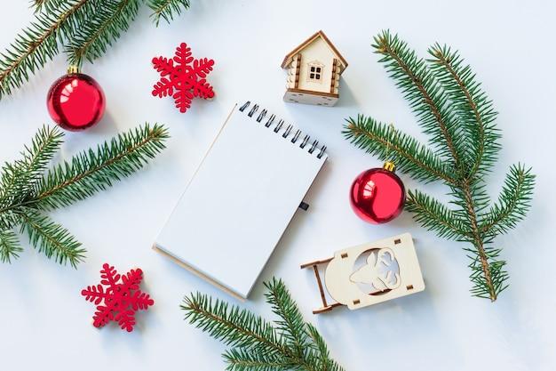 Новогодний или рождественский фон с праздничными украшениями с записной книжкой. вид сверху. плоская планировка. макет.