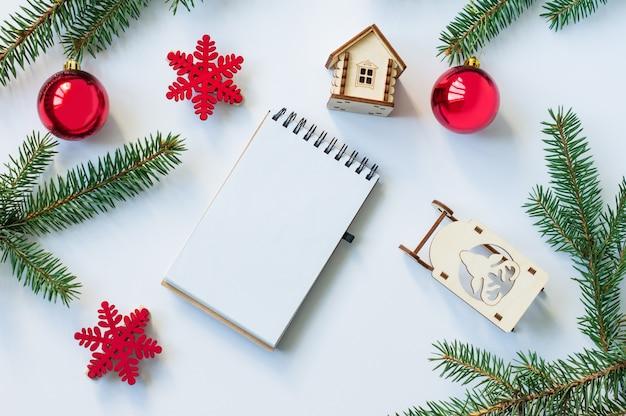 가문비나무 가지, 빨간 공, 나무 썰매, 장난감 집이 있는 새해 또는 크리스마스 배경. 평면도. 모형.