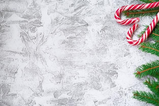 トウヒの緑の枝と新年のハート型のロリポップの新年またはクリスマスの構成。フラットレイ、レイアウト