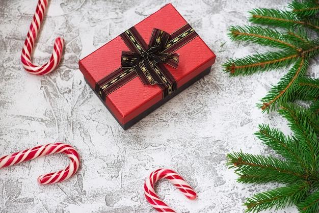 明るいテクスチャの背景にトウヒの緑の枝、ギフト、クリスマスのロリポップの新年またはクリスマスの構成。フラットレイ、レイアウト、フレーム、コピースペース