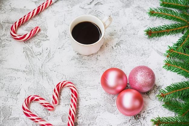 明るいテクスチャの背景にスプルースグリーンの枝、新年のボール、コーヒー、クリスマスのロリポップの新年またはクリスマスの構成。フラットレイ、レイアウト、フレーム、コピースペース