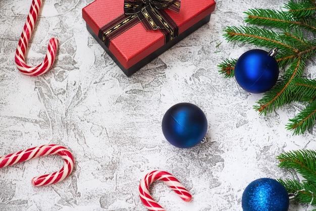 スプルースグリーンの枝、新年のボール、ギフト、クリスマスのロリポップの新年またはクリスマスの構成