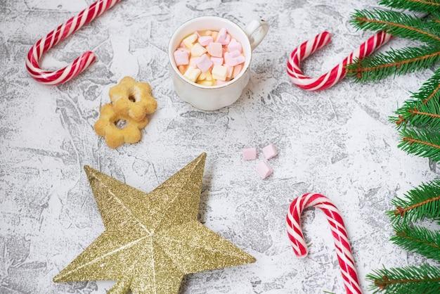 トウヒの緑の枝、元旦の星、マシュマロとロリポップのカップの新年またはクリスマスの構成