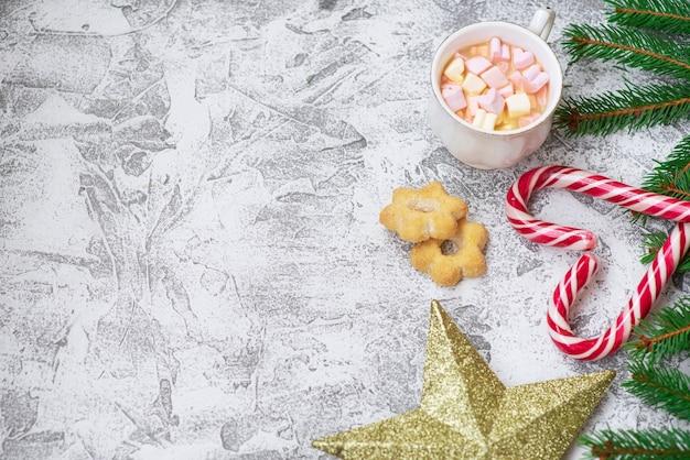 スプルースグリーンの枝、新年の星、明るいテクスチャの背景にマシュマロ、クッキー、クリスマスロリポップのカップの新年またはクリスマスの構成。フラットレイ、レイアウト、コピースペース