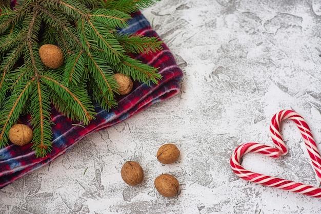 トウヒの緑の枝、赤い格子縞、クリスマスのロリポプソンの新年またはクリスマスの構成は、明るいテクスチャの背景です。フラットレイ、レイアウト、フレーム、コピースペース